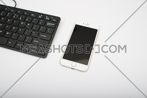 black computer keyboard and mobile phone