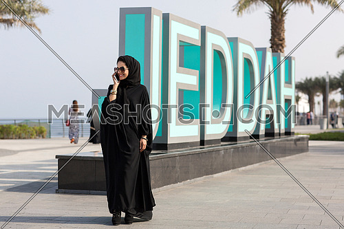 Saudi lady on a call in front of  big (Jeddah) sign at day.