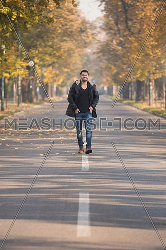 Young Man Walking In Forest Through The Woods Outside During Autumn