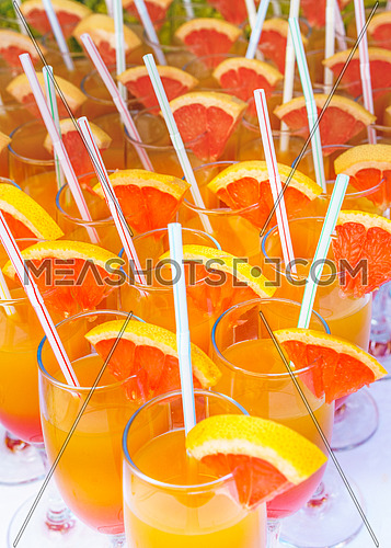 Orange juice cocktail in a flute glasses and slice of fresh orange with draw on white table,closed picture.