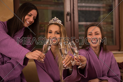 three young beautiful happy girls have a bachelor party at a luxury spa with champagne