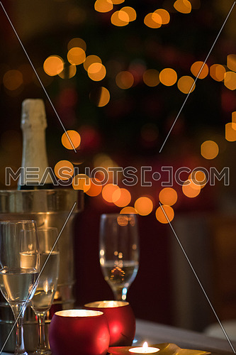 champagne and glasses at home, christmas tree in background , candles new year decoration