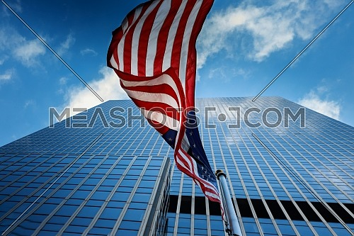 View of American flag waving on blue building background
