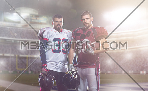 portrait of confident American football players holding ball while standing on big modern american football stadium field with flares and lights
