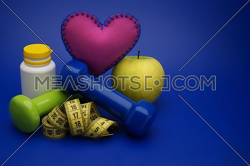 Still life with small dumbbells, measuring tape and fruits, as a concept of healthy nutrition and sports diet in close-up on blue background