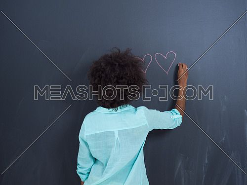 portrait of a beautiful friendly African American woman with a curly afro hairstyle and lovely smile in front of gray chalkboard