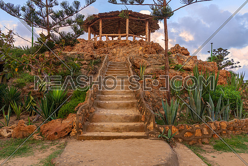 Natural stone stairway with green bushes on both sides leading to wooden pergola with partly cloudy sky at Montaza Park in summer time, Alexandria, Egypt