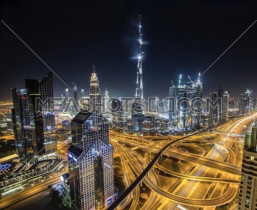 Extreme long shot for Dubai City showing Burj Khalifa and skyscrapers and traffic at night.
