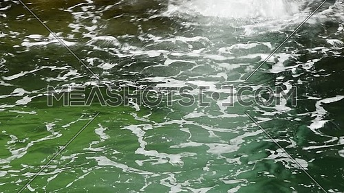 Close up water stream running under waterfall with white foam on surface, high angle view
