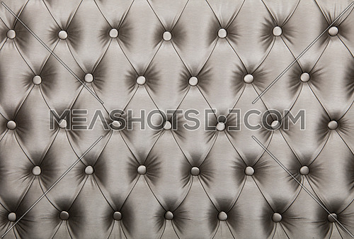 Silver grey capitone textile background, retro Chesterfield style checkered soft tufted fabric furniture diamond pattern decoration with buttons, close up