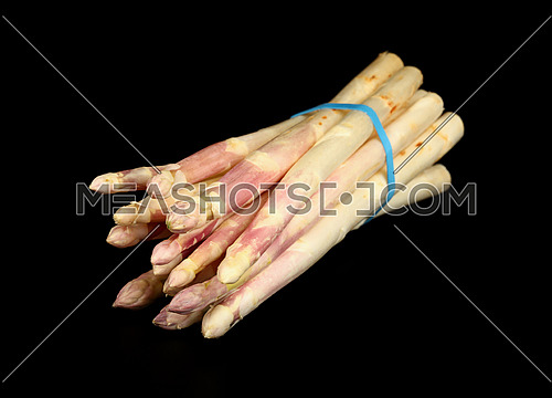 Close up one bunch of fresh white asparagus isolated on black background, high angle view