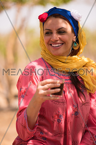 Young beautiful middle eastern woman enjoys the farm grapes with a smile on her face on a sunny summer day