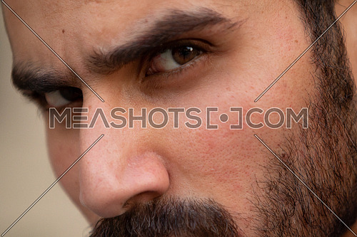 Close up shot for a man's face with a beard.