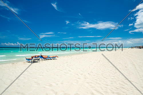 Beautiful beach of Varadero during the day,two tourists lying on sea beds tan,Varadero Cuba.