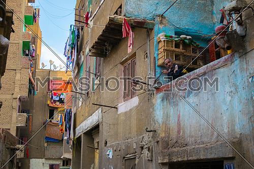 A man sitting in a balcony in a poor neighborhood in old Cairo, Egypt