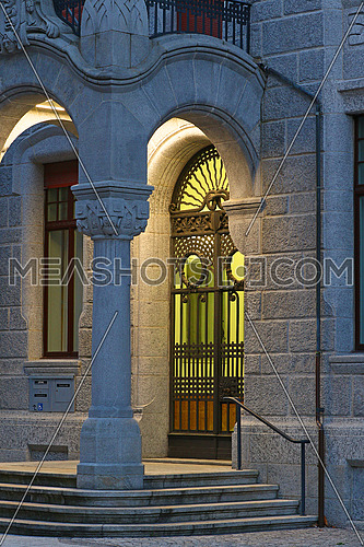 Old forged iron entrance gate to a granite block building