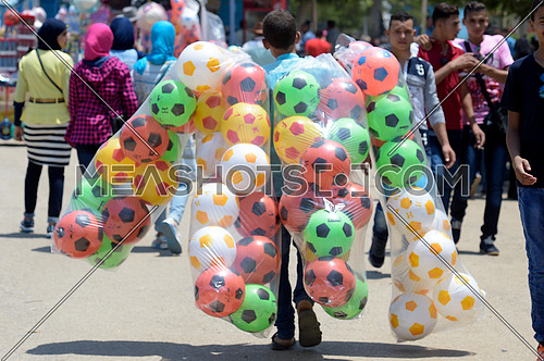 A man carrying colorful balls and selling them to kids during eid al fitr celebrations on july 7 2016
