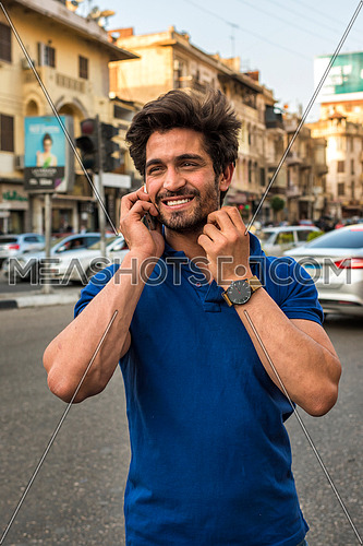young man talking in mobile phone in the street in korba area at day