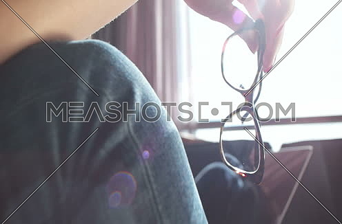 close up of woman holding glasses with sun flare in background