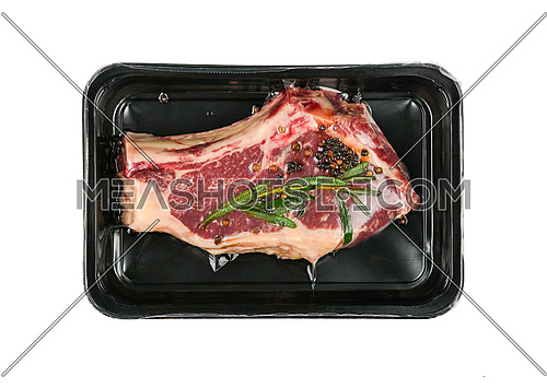 Close up one marbled raw ribeye beef steak with rib bone vacuum sealed with black plastic film, isolated on white background, elevated top view, directly above