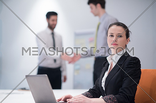 young business woman on meeting usineg laptop computer, blured group of people in background at  modern bright startup office interior taking notes on white flip board and brainstorming about plans and ideas