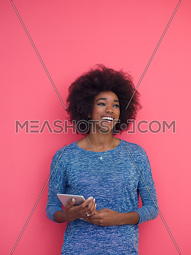 Young Happy African American Woman Using Digital Tablet  Isolated on a pink background
