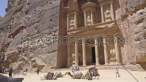 Pan down as tourists walk in front of the Treasury in Petra