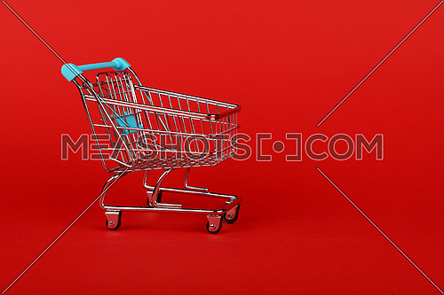Close up empty toy metal supermarket shopping cart over vivid red background with copy space, low angle side view