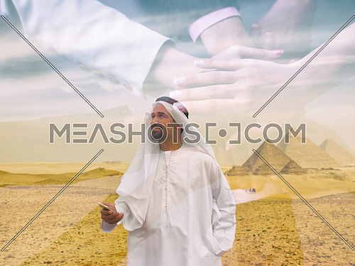 young man as tourist  wearing  arabian traditional clothes in egypt with giza pyramids in background  using smartphone double exposure