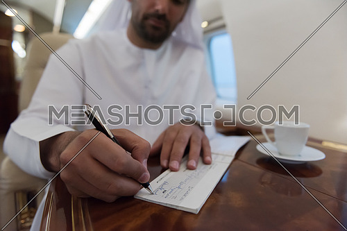 Young middle eastern successful man in traditional clothes writing a check while sitting in private jet