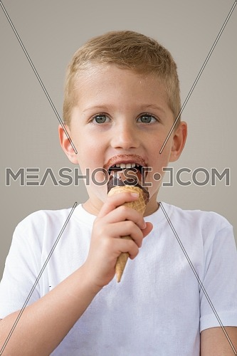 Baby boy kid eating chocolate ice cream in waffles cone isolated on beige background with free text copy space