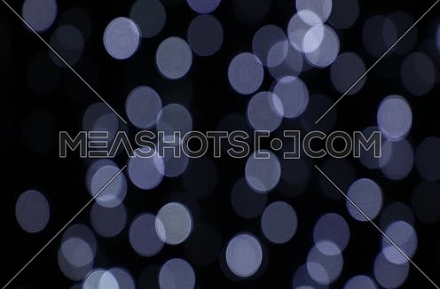 Fast blinking white and light blue festive Christmas circular bokeh over dark, abstract background