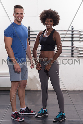 portrait of a young beautiful African American women in sports clothes after a workout at the gym with a trainer