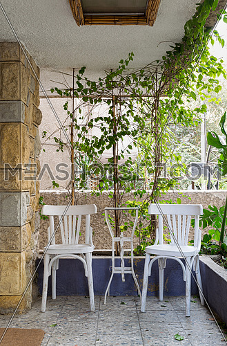 Outdoor leisure corner with two wooden white chairs and metal table in a background of climber plants and stone bricks wall
