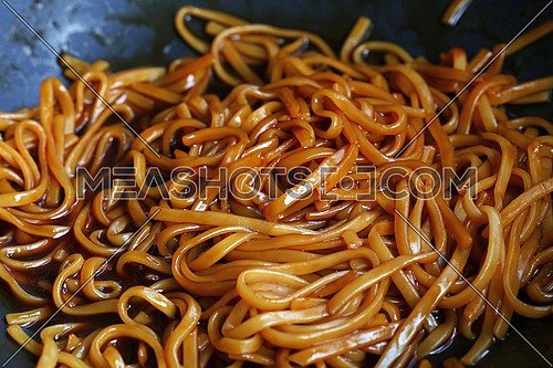 Cooking Asian traditional meal of stir fried udon noodles with soy sauce in wok pan, close up, high angle view