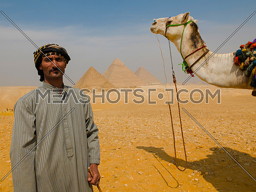 A man with his camel at the pyramids of giza