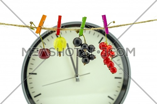 Clock showing five minutes to twelve with fresh a cherry, gooseberry, red and black currants hanging on a line from clothes pegs in a healthy diet concept with copy space over white