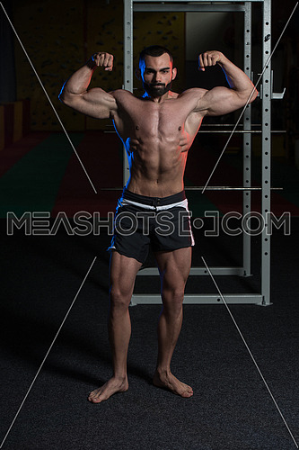 Young Man Standing Strong In The Gym And Performing Front Double Biceps Pose - Muscular Athletic Bodybuilder Fitness Model Posing Exercises