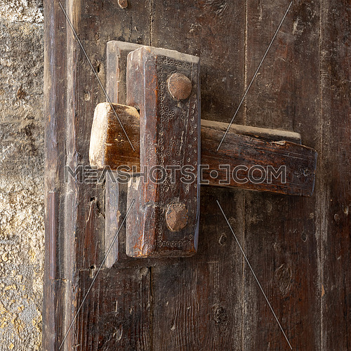 Angled view closeup of a wooden aged latch over a wooden opened door