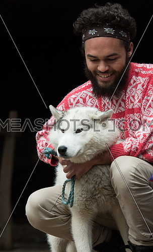 handsome young hipster man playing with white husky dog in front of old vintage retro wooden house
