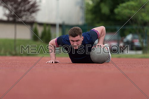 Young Man Outdoors Performing Push Ups On Medicine Ball Bodybuilding Exercise