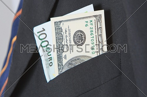 Dollars and Euros in the pocket of a suit