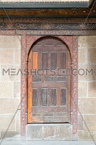 Wooden aged vaulted door and stone wall, Medieval Cairo, Egypt