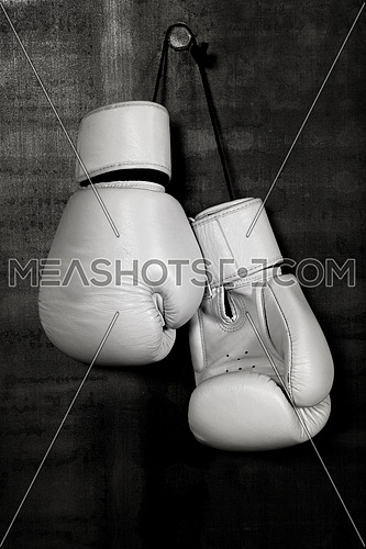 Close up pair of white leather boxing gloves hanging over black wall with copy space