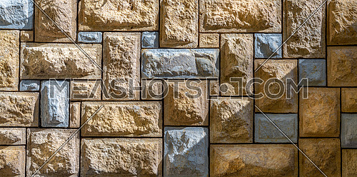 Background of pattern of beige and gray decorative uneven stone wall surface