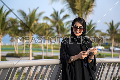 Saudi lady smiling and holding her phone