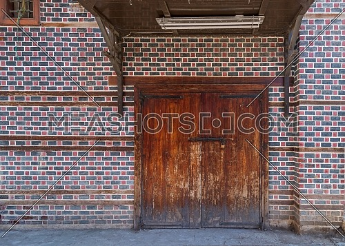 Grunge wooden decorated arched entrance gate with wooden canopy above on wall with black and red bricks with white seam