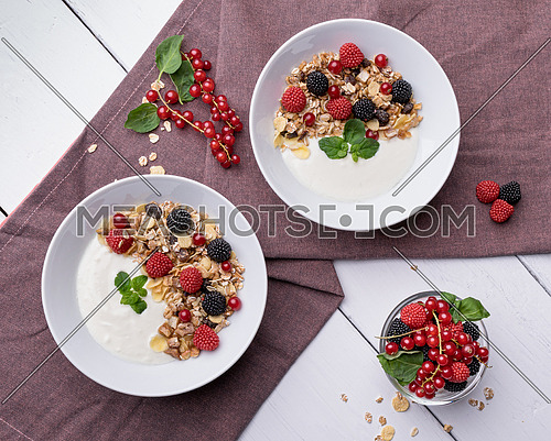 Healthy breakfast of two bowls with yogurt, muesli, raspberry and cherries on a background of violet tablecloth and white table