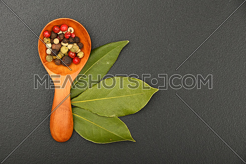 Group of three bay laurel leaves and mix of peppercorn in wooden scoop on black chalkboard background