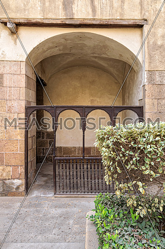 Embedded space with wooden balustrade and wooden arches behind a planted flower box at the external wall of an old historic house (Beit El sehemy), Cairo, Egypt